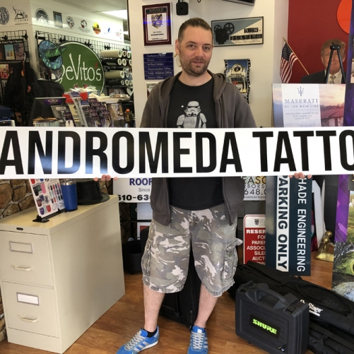 Andromeda Tattoo Sign Held by Customer