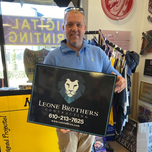 Leone Brothers Sign Held by Customer